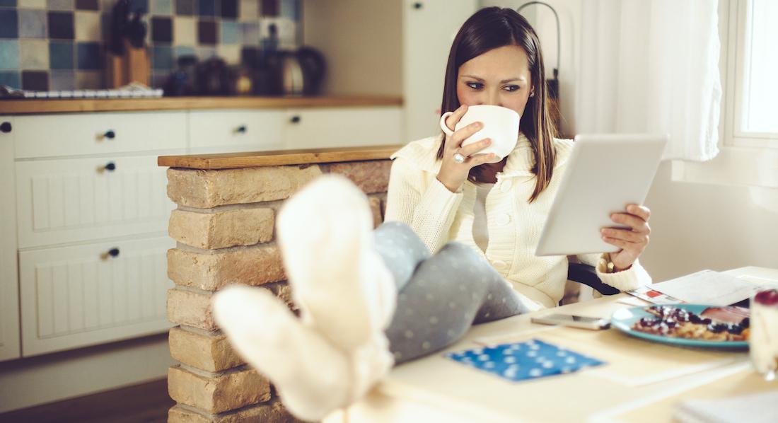 Eine junge Frau sitzt entspannt bei einer Tasse Kaffee in der Küche und nutzt auf ihrem Tablet ein TAN-Verfahren für den Online-Einkauf