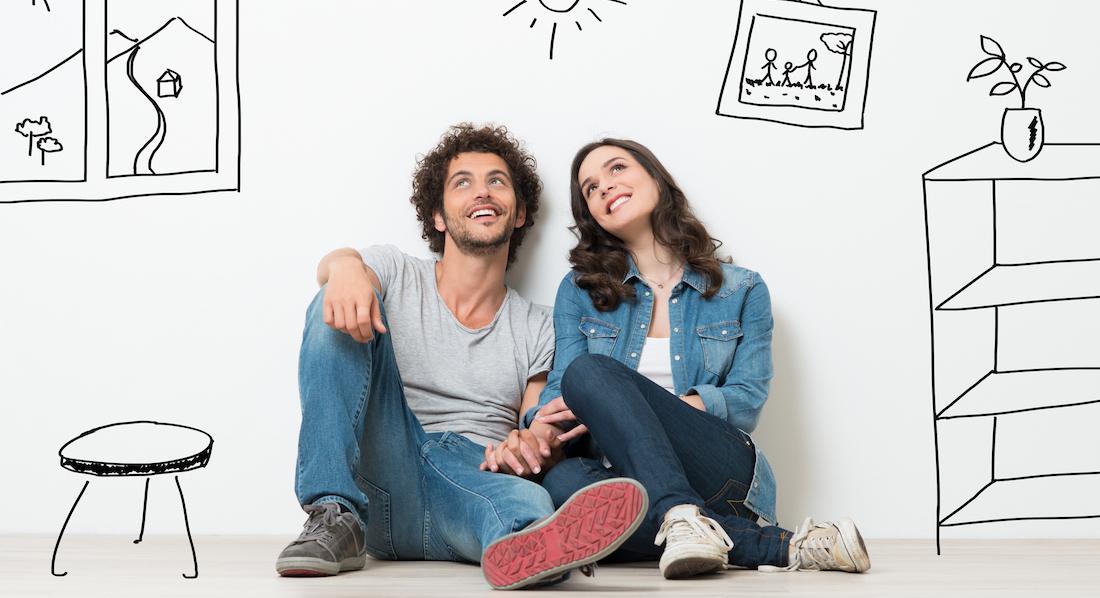 Junges Paar sitzt im leeren Raum, per Wandzeichnungen ist die Einrichtung dargestellt, für die es sich einen Kredit leisten will