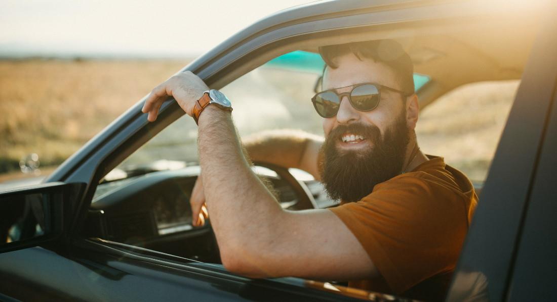 Junger Mann mit Sonnenbrille und Vollbart blickt lächelnd aus dem Autofenster