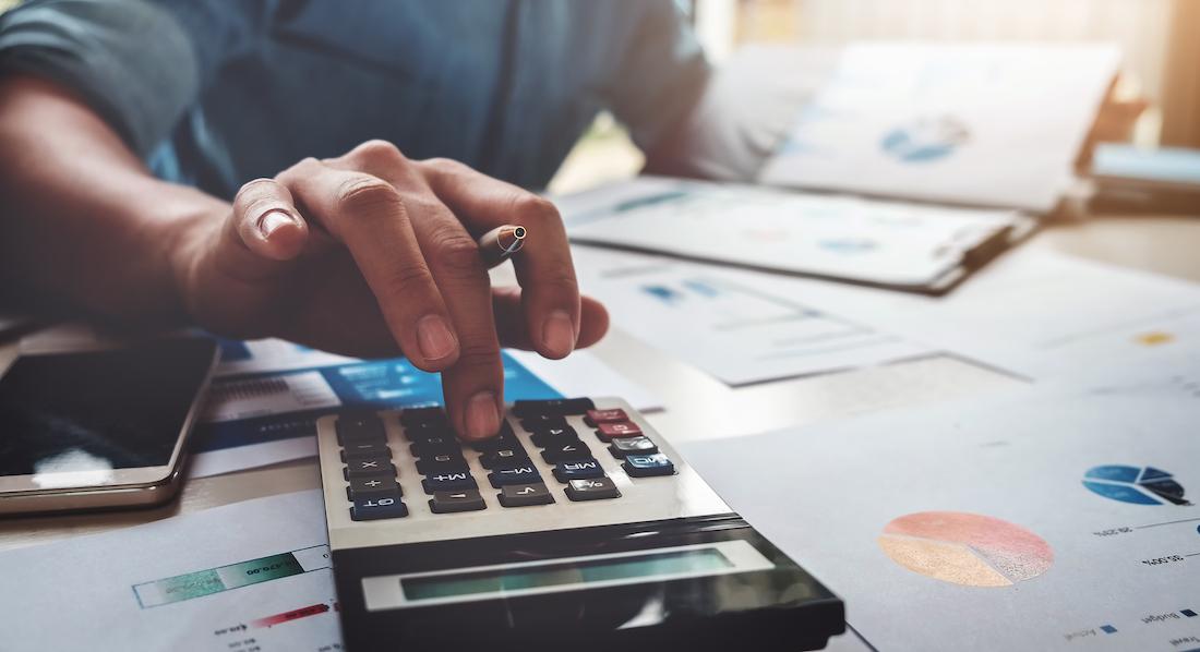 Ein junger Mann berechnet mit Taschenrechner seine Rentenlücke