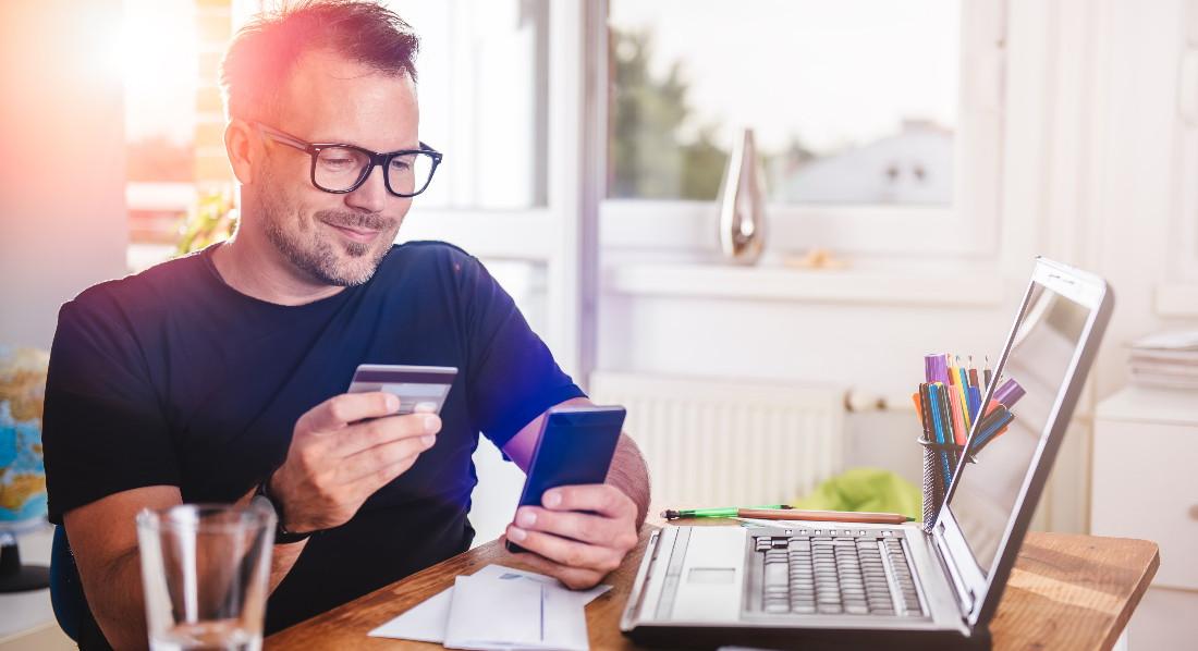 Junger Mann liest auf dem Smartphone seine TAN für die Online-Bezahlung mit Verified by Visa ab.