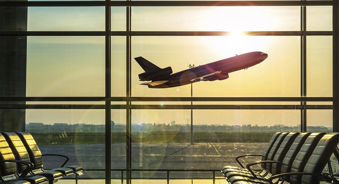 Blick aus einem leeren Flughafen Terminal auf ein abhebendes Flugzeug