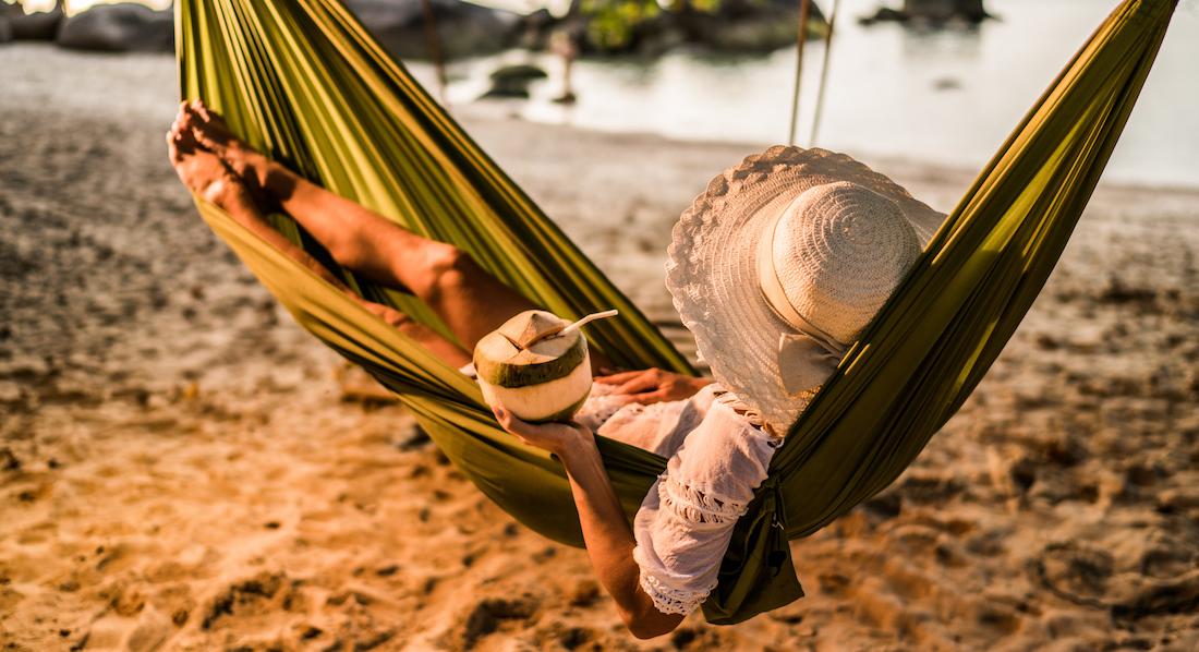 Frau entspannt mit einem Drink in einer Kokosnuss in einer Hängematte an einem exotischen Strand