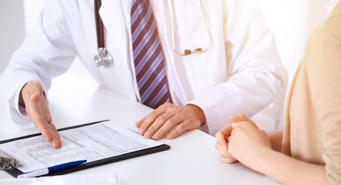 Ein Arzt erklärt einer Frau, dass sie dauerhaft arbeitsunfähig ist und es sinnvoll ist, ihre Berufsunfähigkeitsversicherung darüber zu informieren
