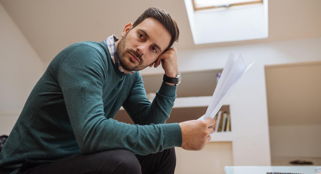 Mann sitzt mit traurigem Gesicht auf dem Sofa, in der Hand Papiere von der Berufsunfähigkeitsversicherung