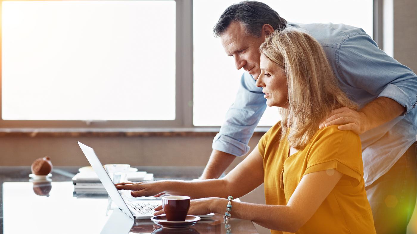 Ein Paar recherchiert gemeinsam mittels eines Notebooks, ob seine Hausratversicherung steuerlich absetzbar ist