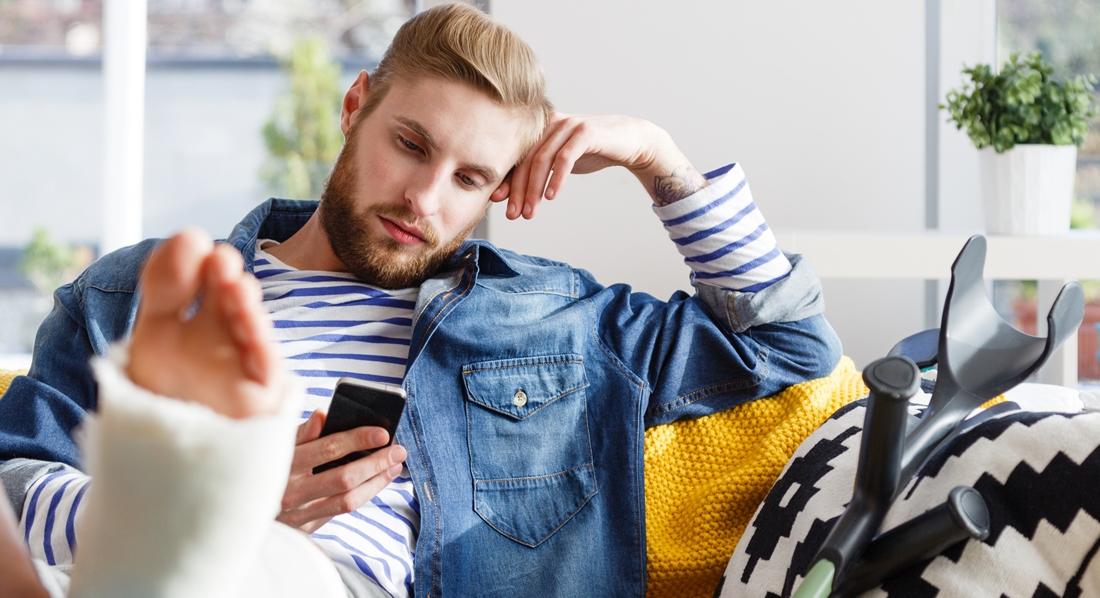 Junger Mann mit Gipsbein erkundigt sich nach seiner Reiserücktrittsversicherung