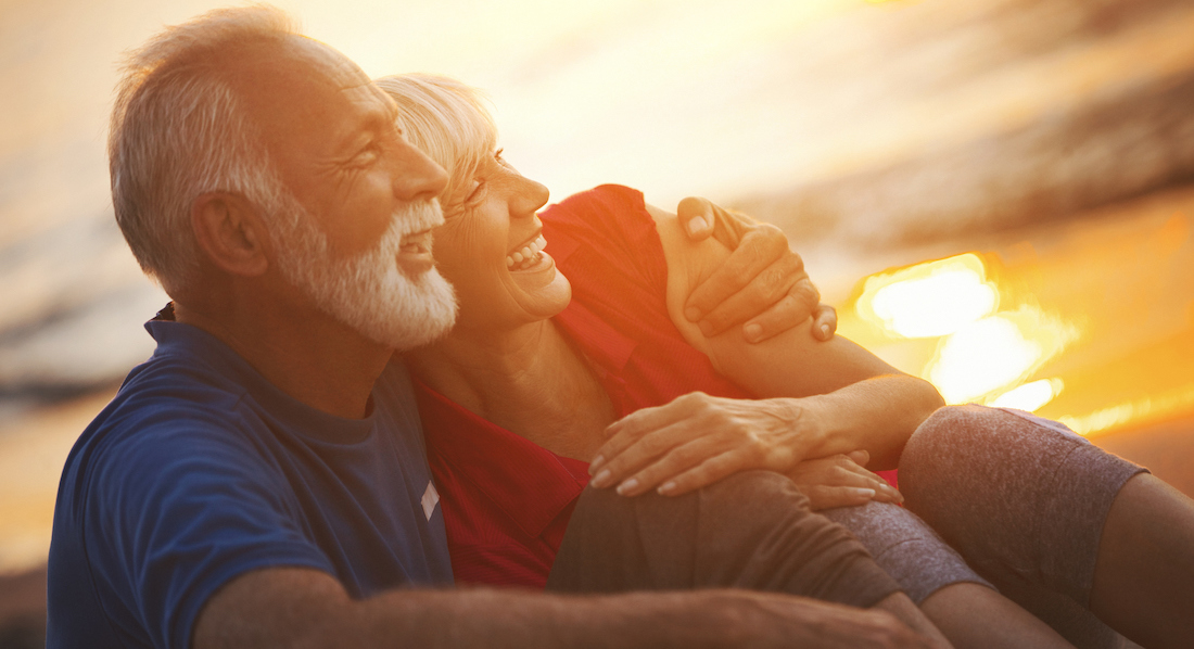 Senioren-Pärchen blickt lächelnd Arm in Arm in den Sonnenuntergang
