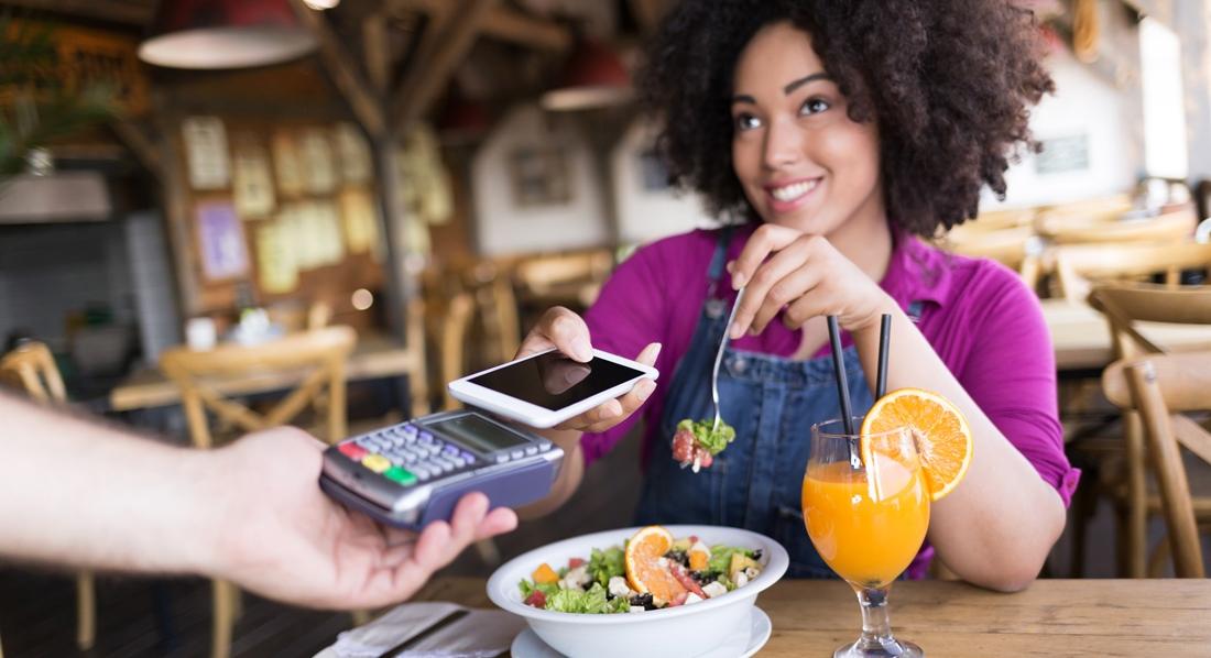 Frau bezahlt am Tisch im Restaurant einen Salat, indem sie ihr Handy über ein Lesegerät hält.