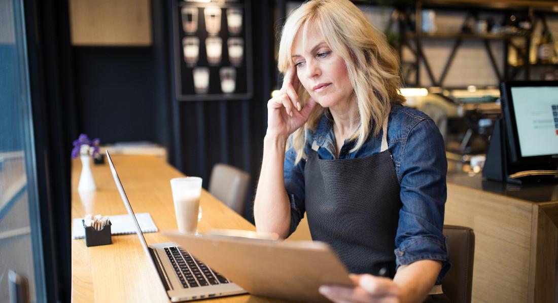 Eine weibliche Bedienung in einem Café blickt besorgt auf ein Notebook.