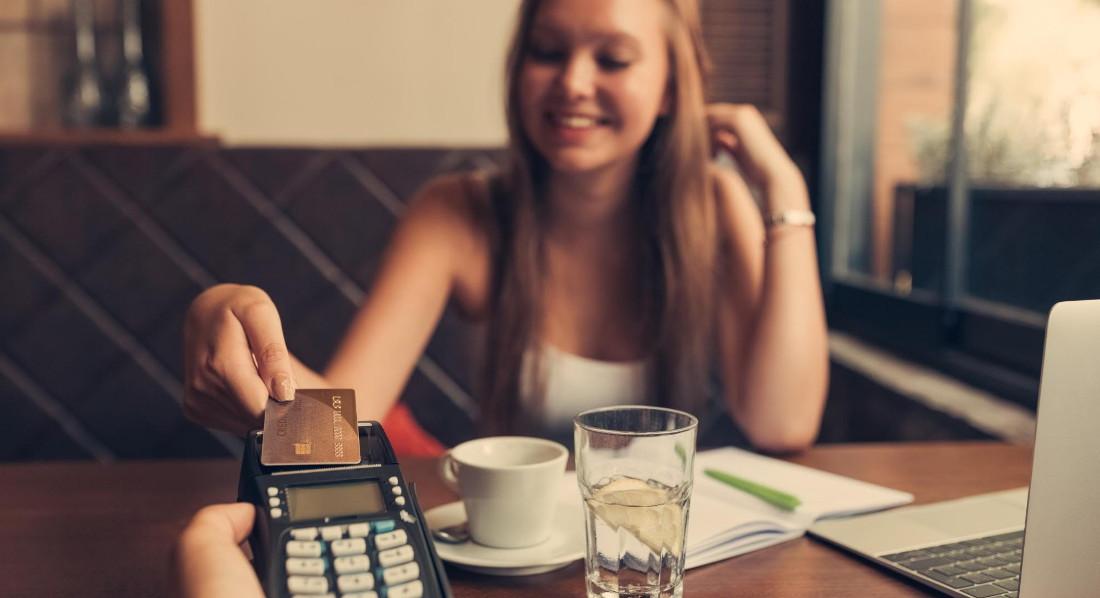 Eine Teenagerin bezahlt in einem Bistro ihren Kaffee mit einer Kreditkarte
