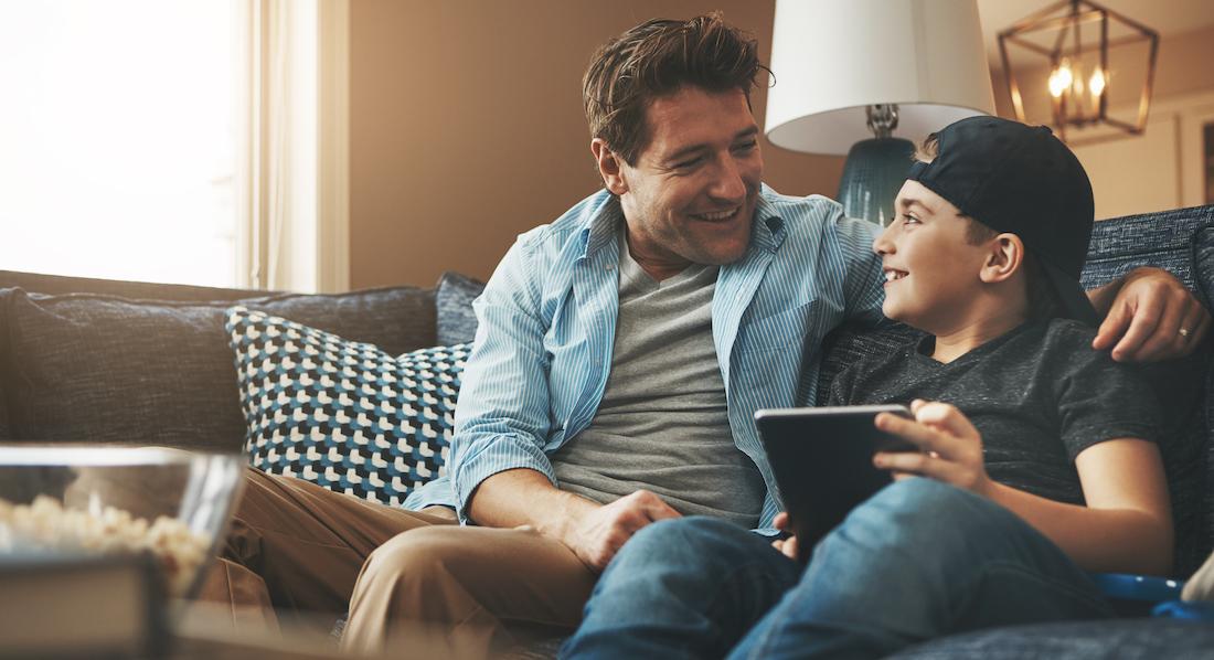 Vater und Sohn sitzen mit Tablet auf einem Sofa und unterhalten sich über Bank-Apps