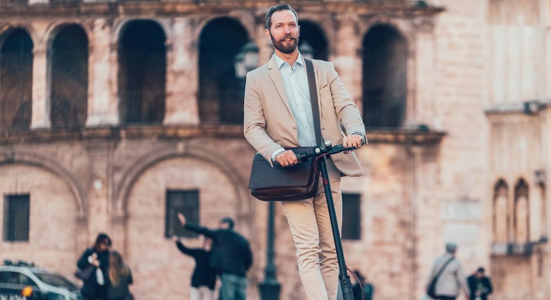 Bärtiger Mann im hellen Anzug fährt auf einem Elektroroller durch die Straßen; im Hintergrund ist eine spanische Altstadt erkennbar