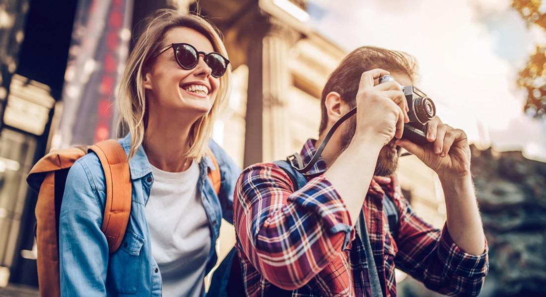 Ein Paar lacht und macht Urlaubsfotos.