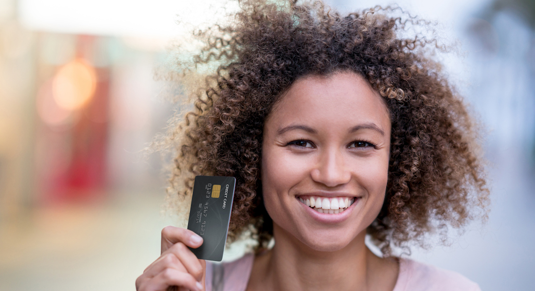 Junge Frau hält lächelnd Kreditkarte in der Hand