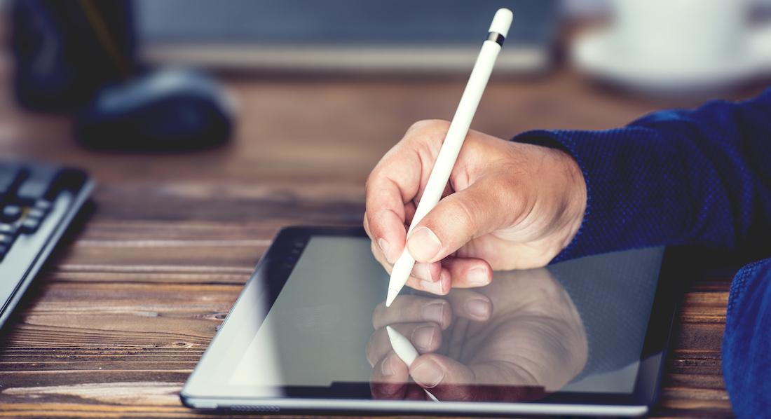 Mann schreibt mit Stift auf einem Tablet
