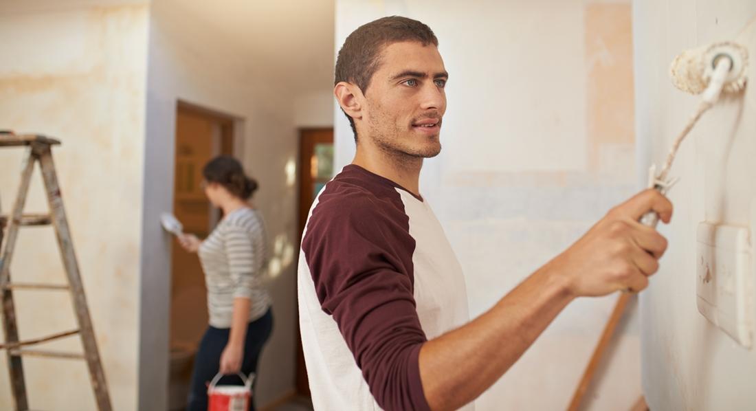 In einer leeren Wohnung führt ein junger Mann einen Farbroller auf einer hellen Wand.