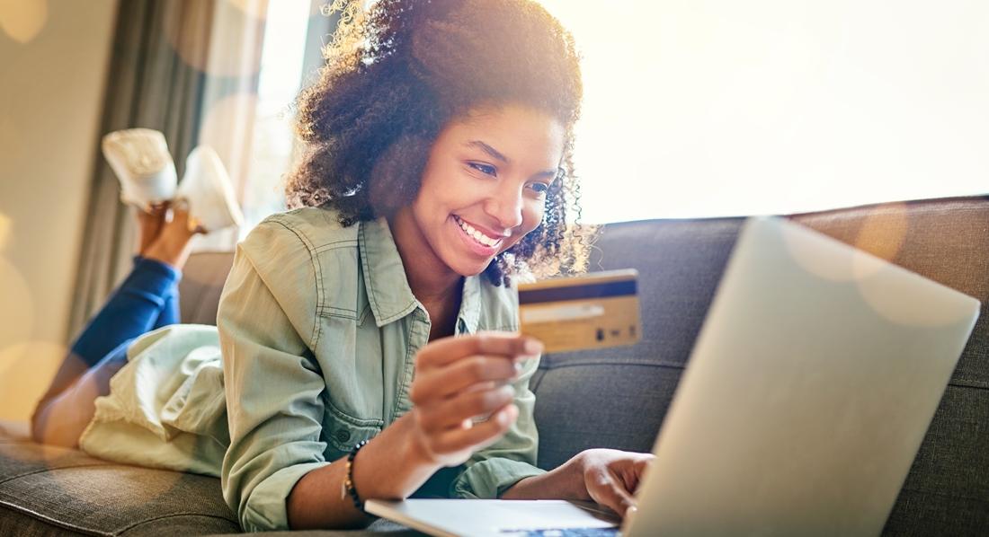 Junge Frau liegt mit Laptop auf dem Sofa und nutzt die Kreditkarte zum Online Shopping