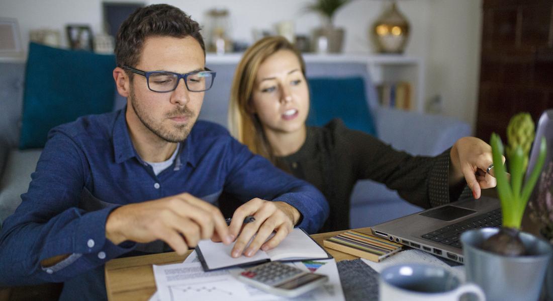 Ein Paar schaut auf einige Papiere und berechnet die Zinsen bei einem Tagesgeldkonto