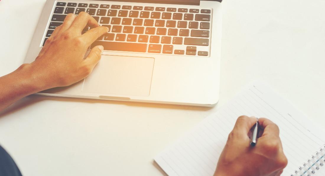 Eine Frau tippt ihren Antrag auf eine Renteninformation mit der linken Hand in einen Laptop und macht sich Notizen mit der rechten Hand.
