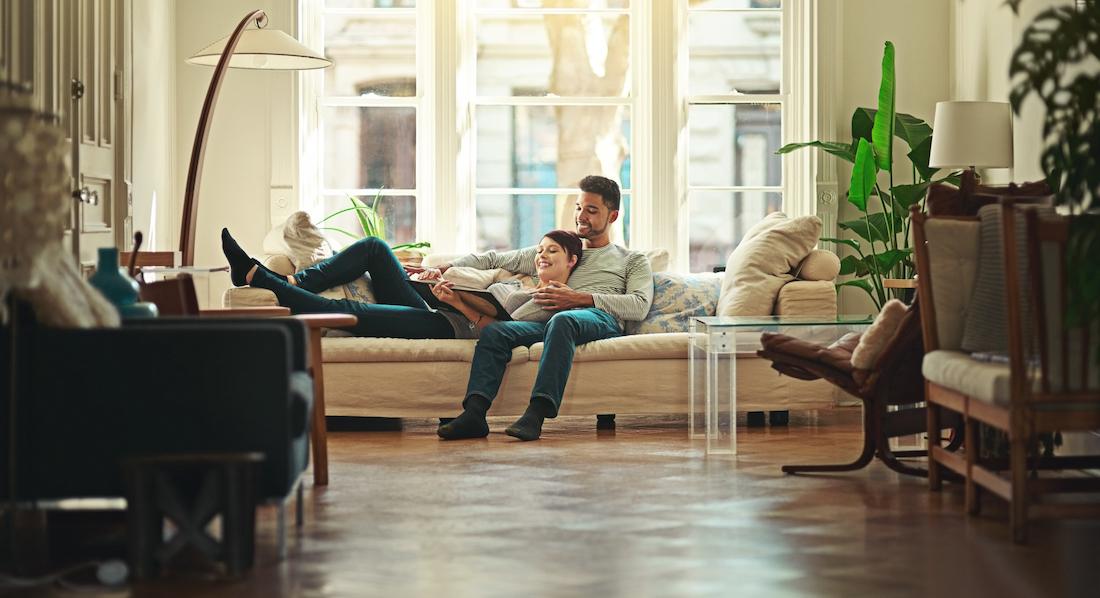 Hausratversicherung: Glücklich wirkendes junges Paar auf einem hellen Sofa in einer geschmackvoll möblierten Altbauwohnung beim Betrachten eines Buches