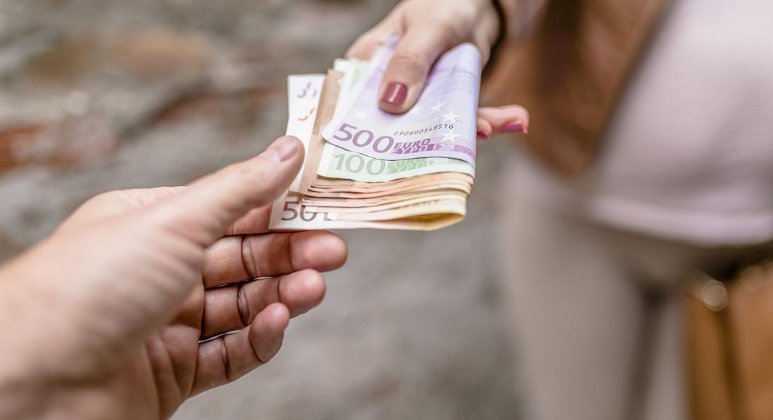 Nahaufnahme einer Frauenhand, die ein Bündel Euro-Banknoten übergibt.