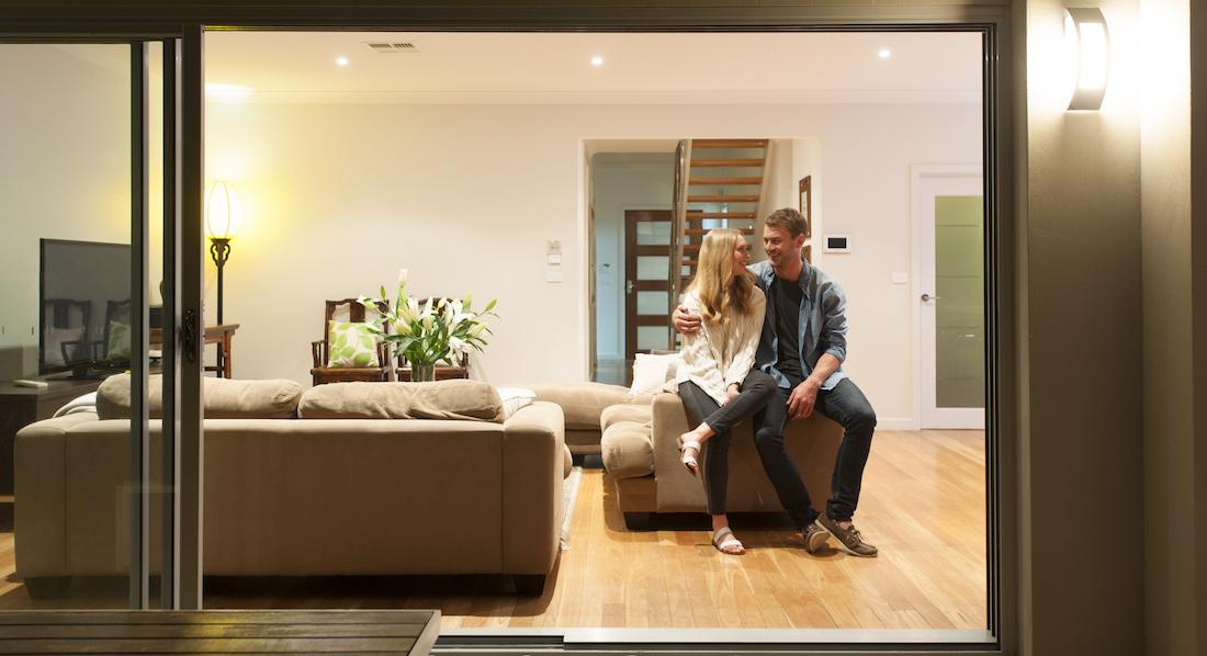 Junges Paar sitzt Arm in Arm auf dem Sofa in der lichtdurchfluteten modernen Wohnung, für die es sich einen Kredit geleistet hat