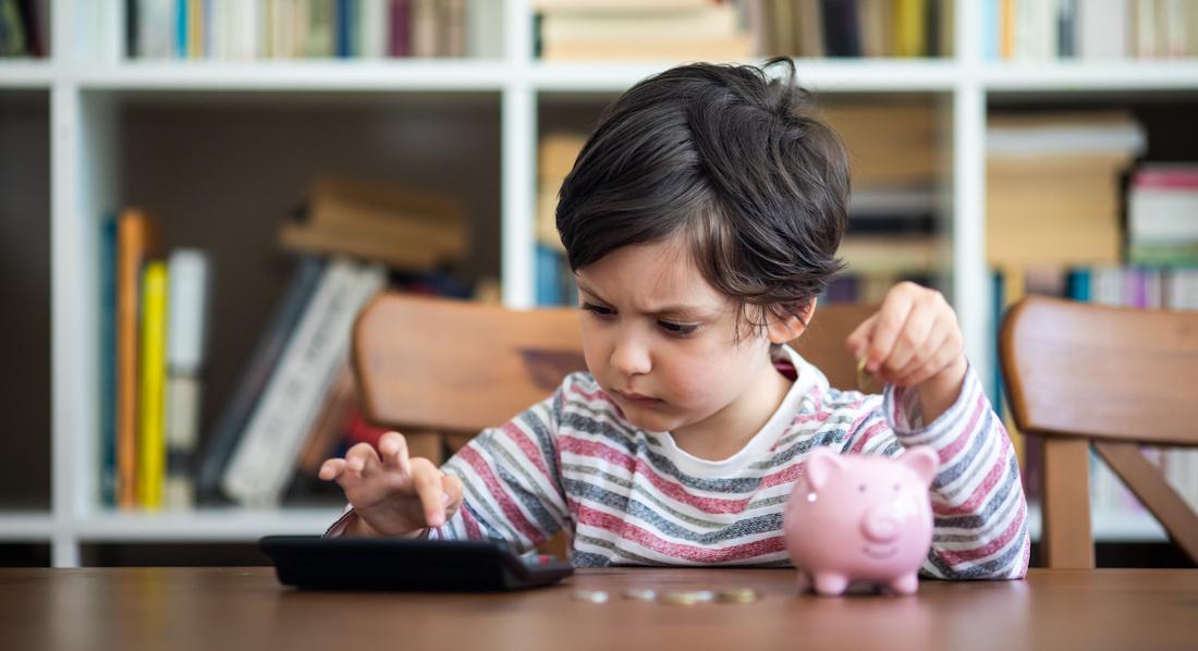 Kleines Mädchen wirft mit der einen Hand eine Münze in ein Sparschwein und rechnet die angesparte Summe mit der anderen Hand auf dem Taschenrechner zusammen