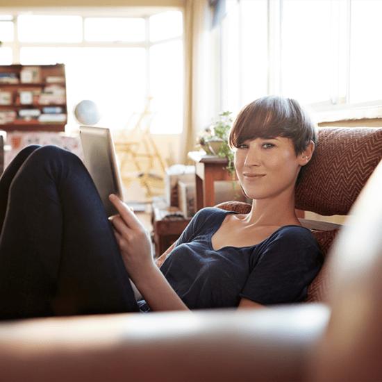 Frau sitzt auf Sofa mit Tablet