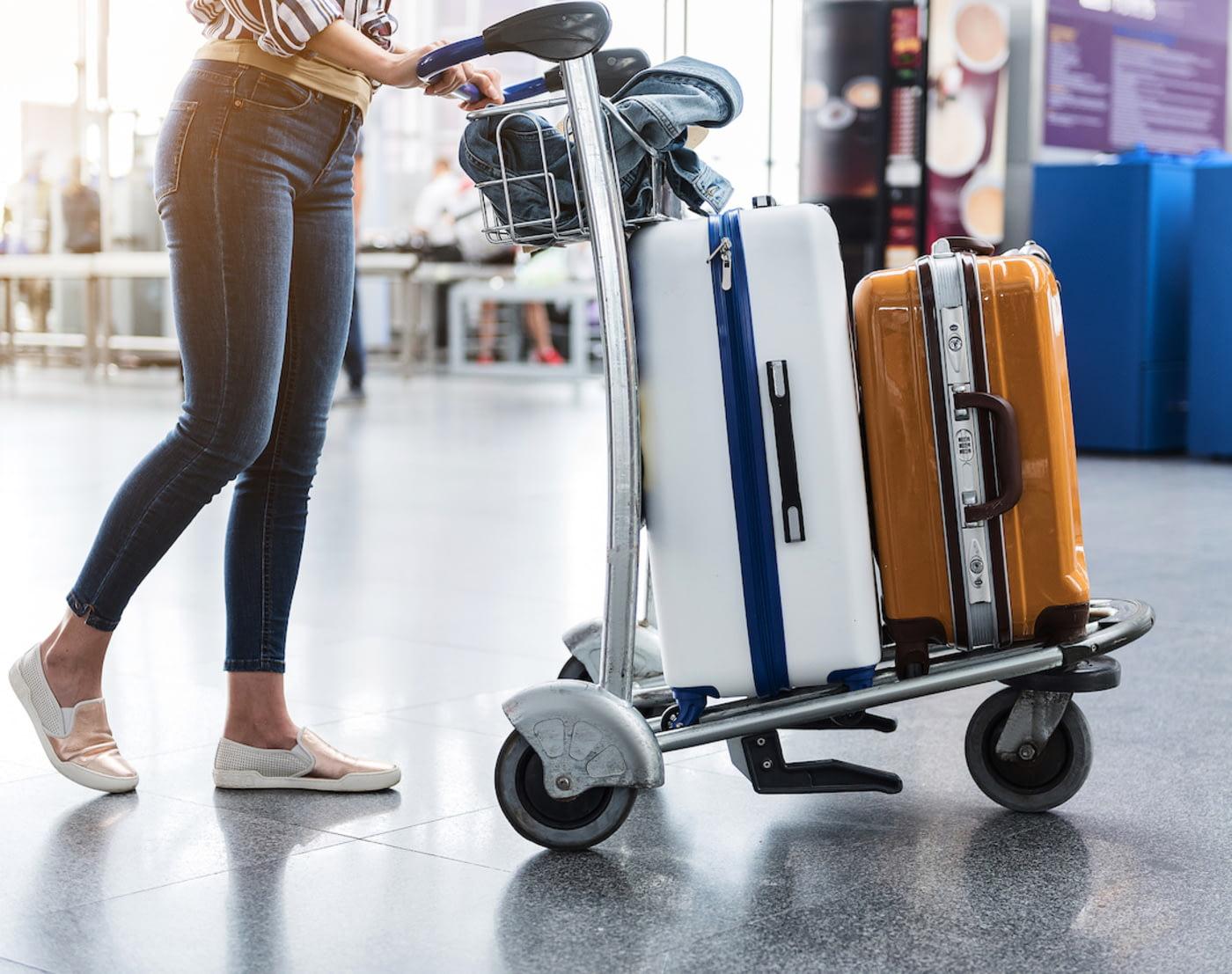 Frau schiebt Kofferkuli voll mit Gepäck durch den Flughafen