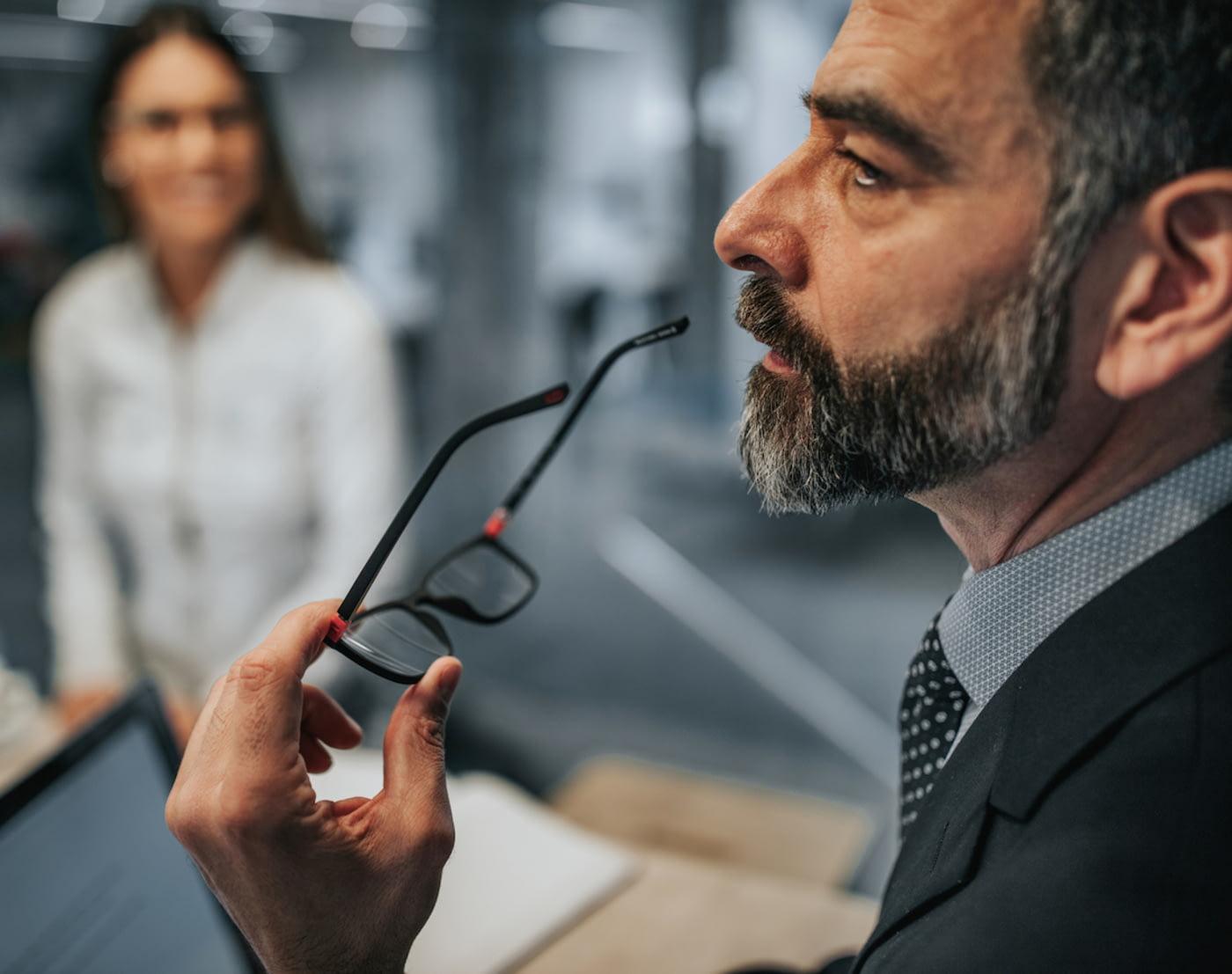 Geschäftsmann mit graumeliertem Haar und gepflegtem Bart denkt mit Brille in der Hand nach