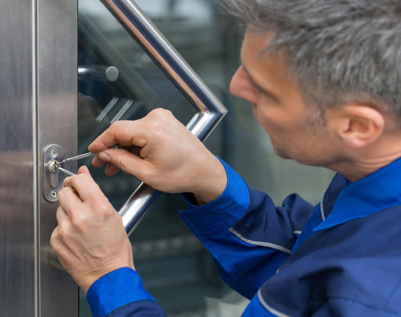 Ein Handwerker versucht, mit Spezialwerkzeug eine Tür zu öffnen