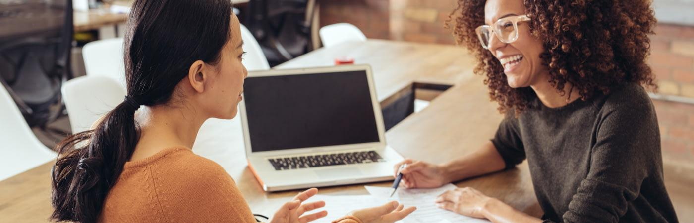 Eine junge Frau erklärt einer anderen Frau etwas an einem Tisch mit Papier und Laptop