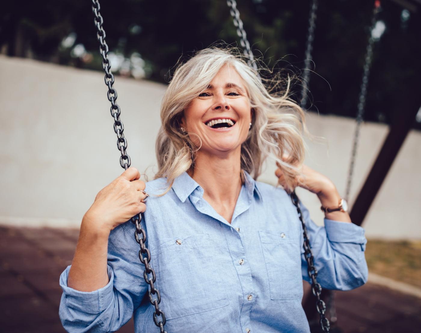 Rentenlücke schließen: Frau mit grauen Haaren sitzt lachend auf einer Schaukel