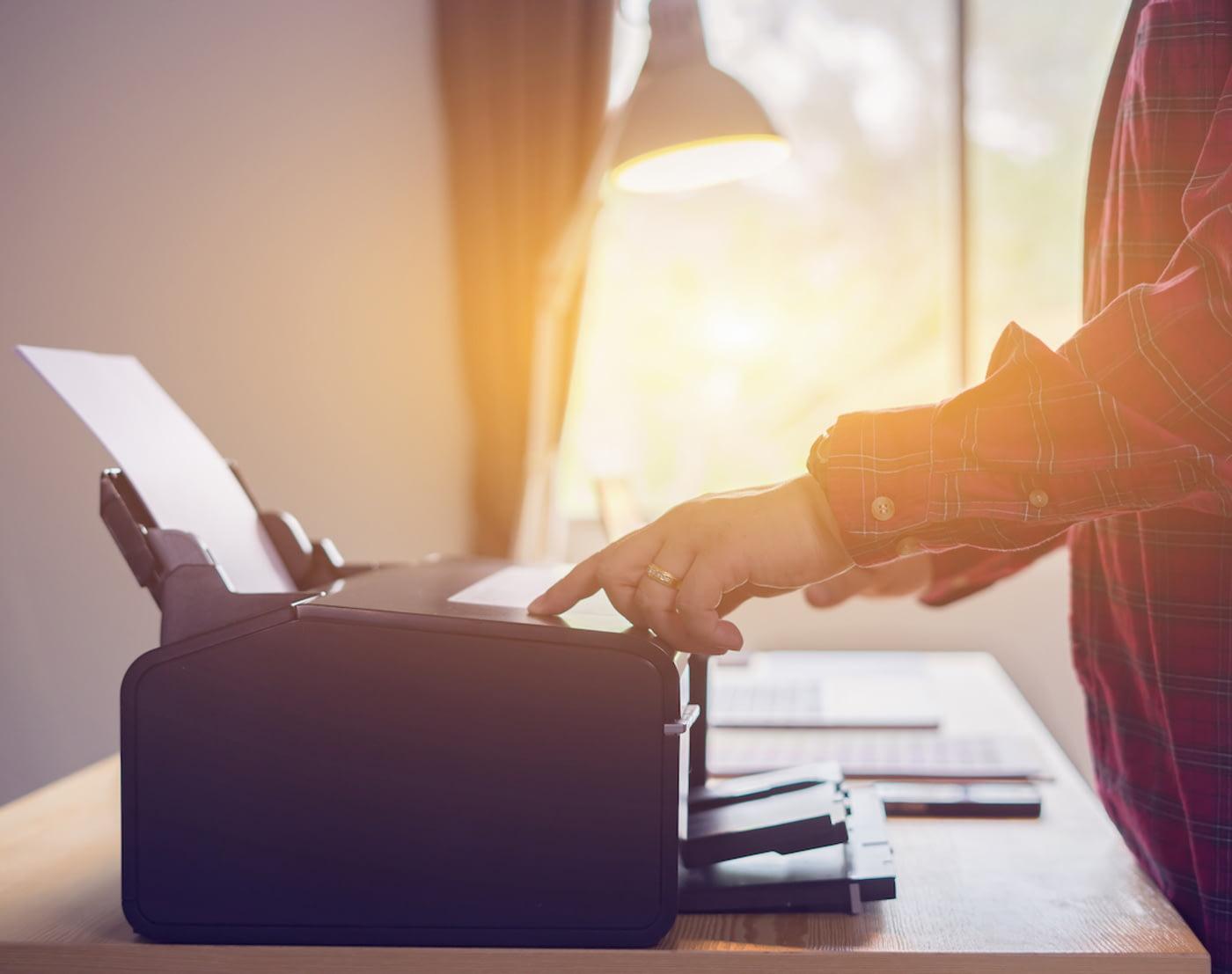 Ein Mann bedient einen Drucker, um eine Vorlage zur Kündigung seiner Versicherung auszudrucken