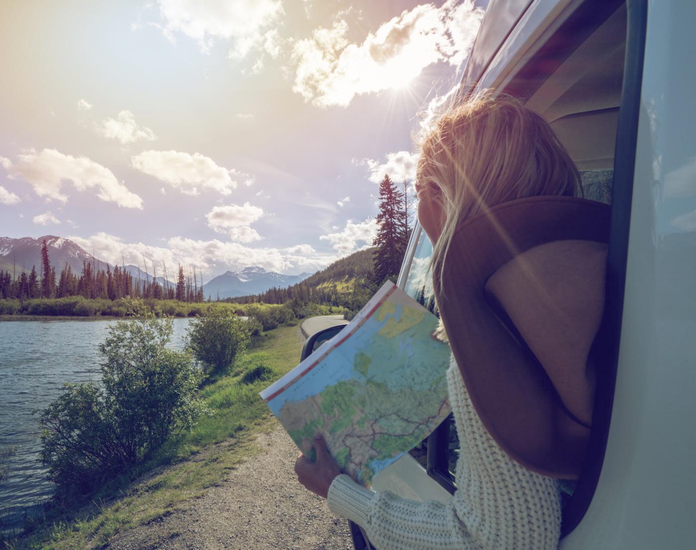 Frau schaut aus dem Seitenfenster eines an einem Fluss geparkten Wohnmobils, im Hintergrund eine Bergkulisse