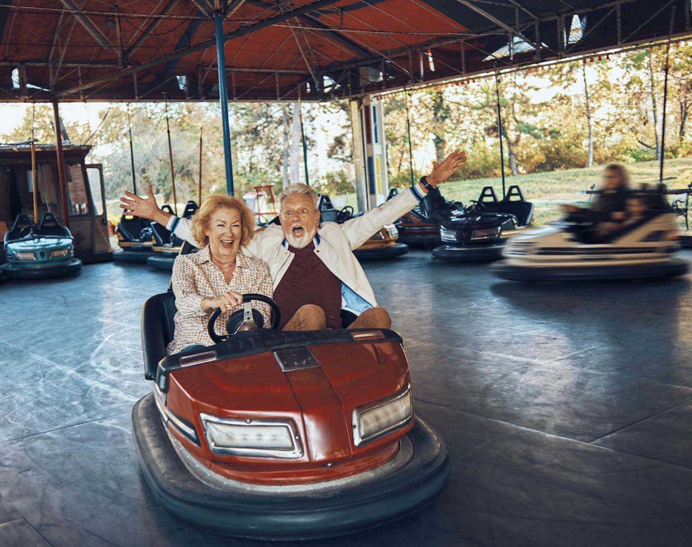 Älteres Pärchen fährt vergnügt Autoscooter; sie sitzt am Steuer, er reißt freudig die Arme in die Luft