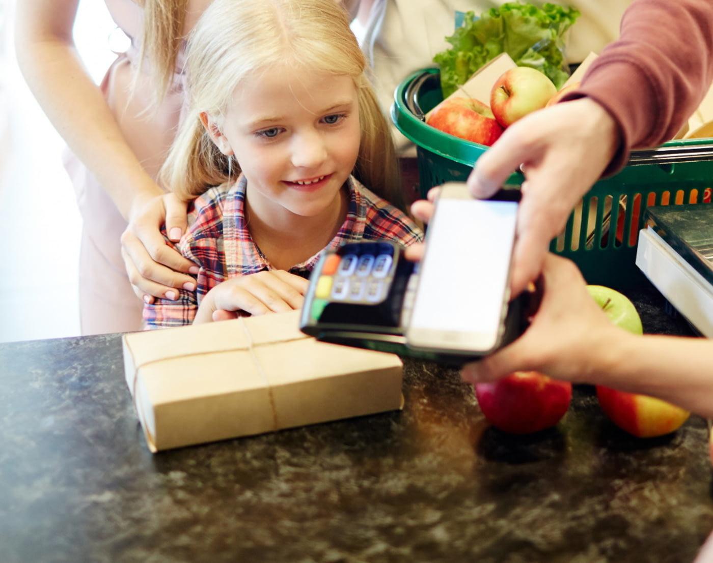 Familie beim Bezahlen im Supermarkt.
