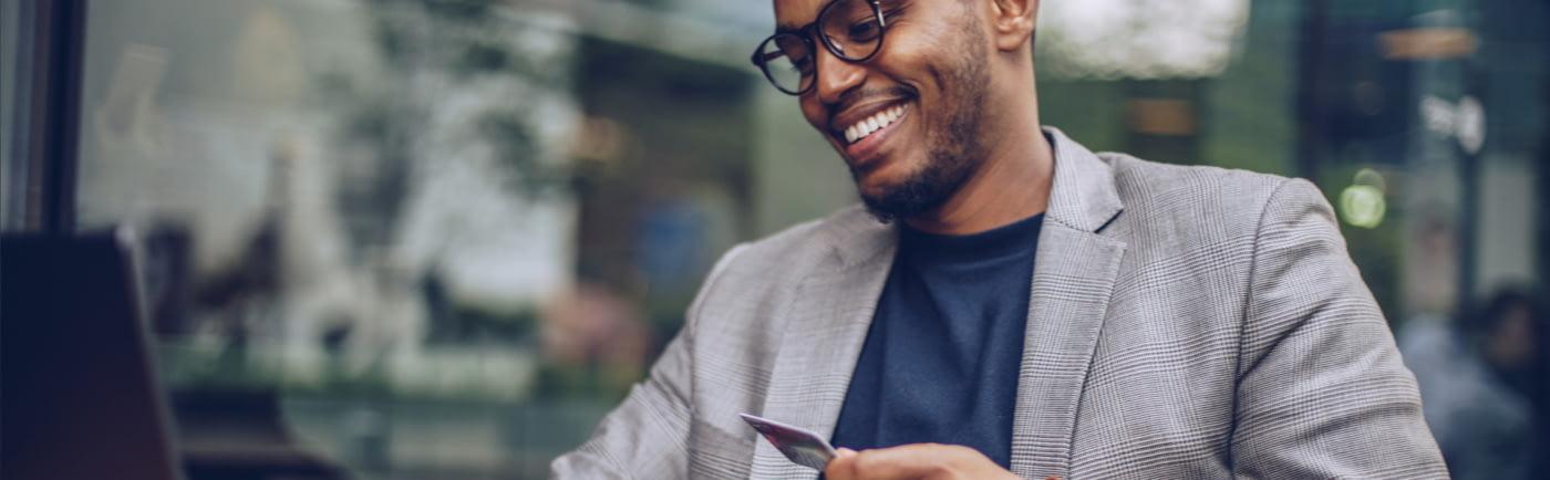 Junger Mann sitzt mit gezückter Kreditkarte in Straßenszenerie vor seinem Laptop