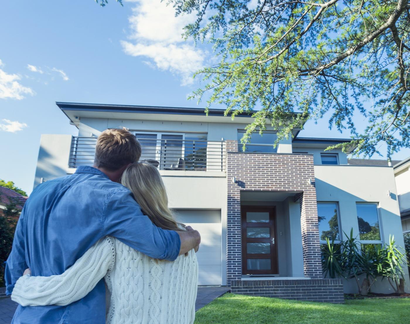 Das Haus ist versichert: Ein Ehepaar steht Arm in Arm und blickt auf sein Haus