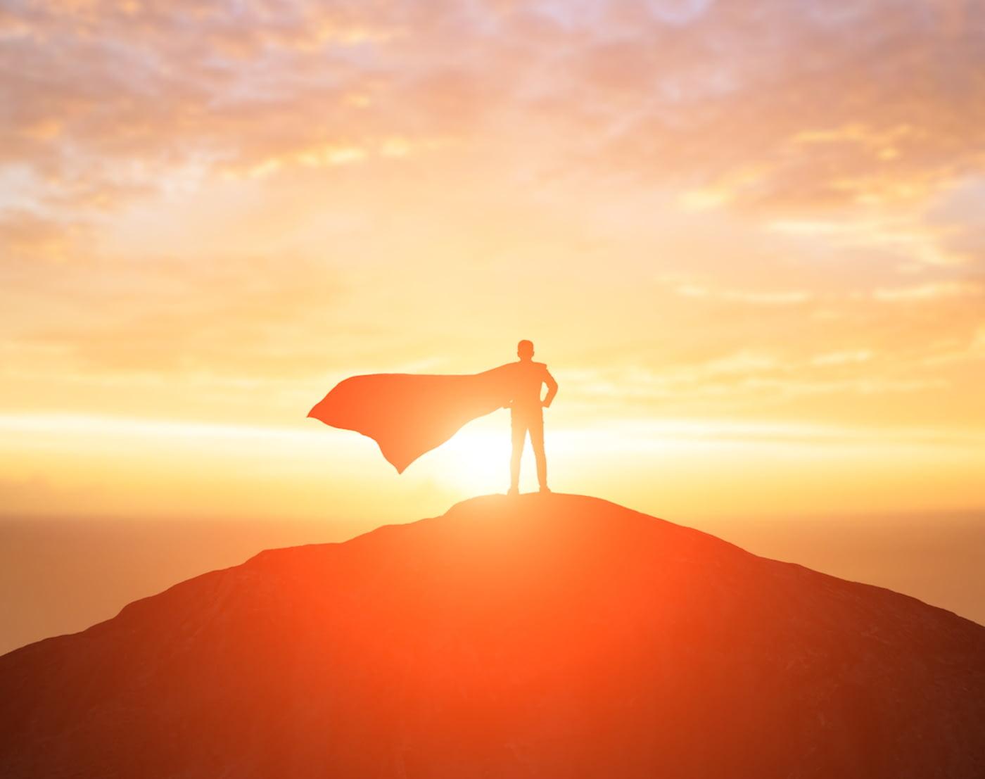 Mann mit Superhelden-Umhang steht auf einem Hügel vor dem Sonnenuntergang