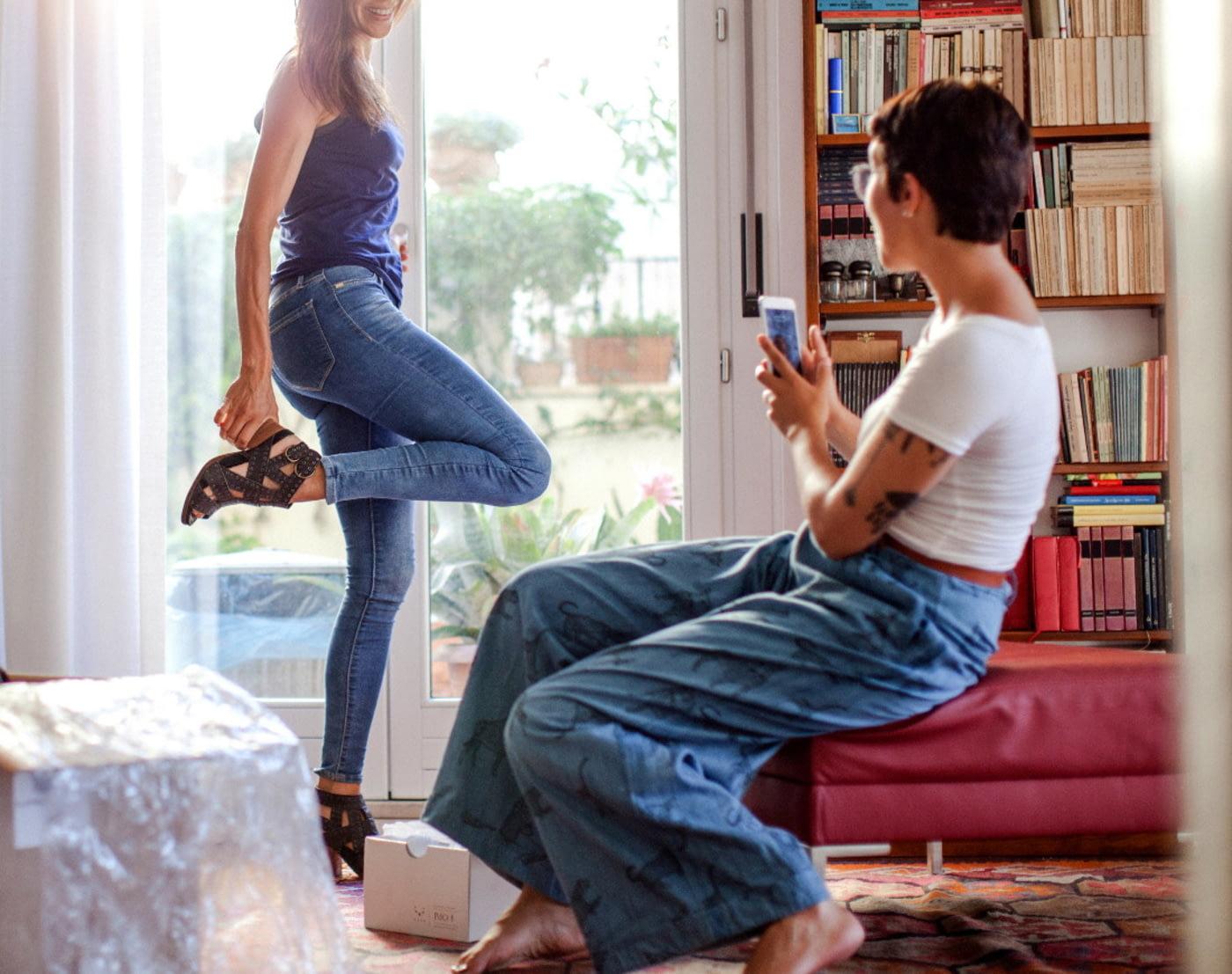 Frau probiert zu Hause neue Schuhe an, ihre Freundin fotografiert