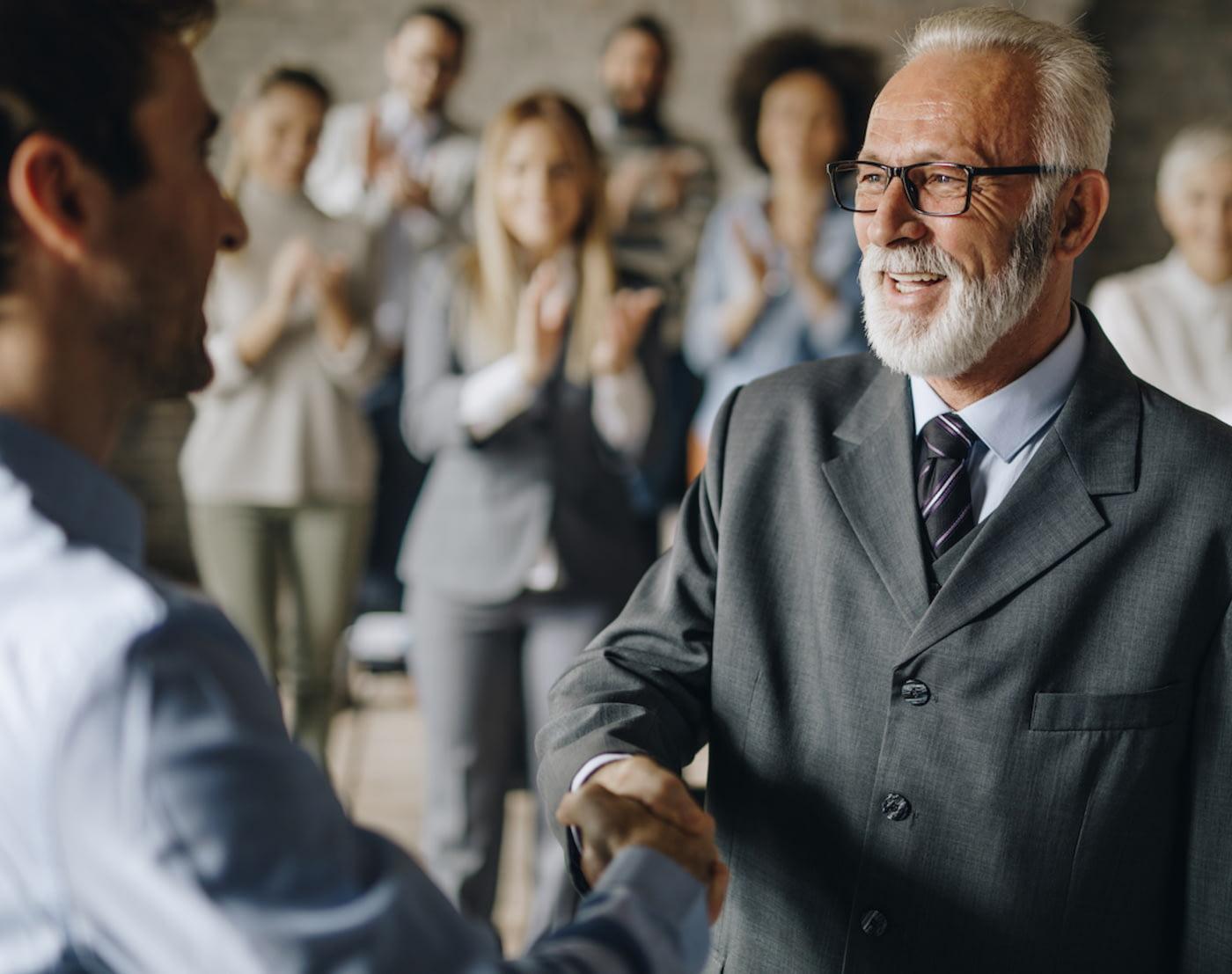 Älterer Mann wird von jüngerem Mann in den Ruhestand verabschiedet, im Hintergrund klatschen die Kollegen