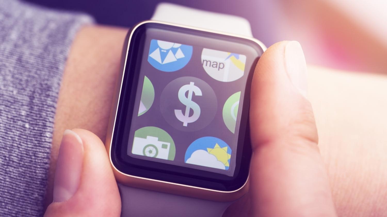 Mann tippt auf Smartwatch am Handgelenk, auf der ein Dollar-Zeichen zu sehen ist
