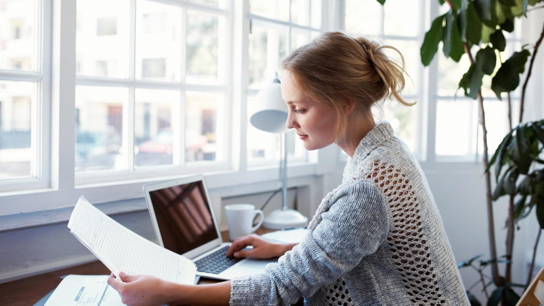 Eine Frau sitzt am Schreibtisch und prüft Dokumente