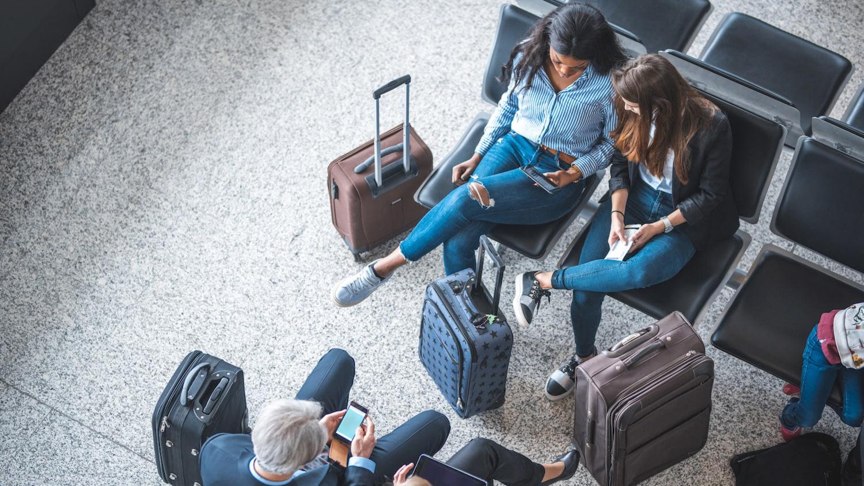 Frauen mit Koffern unterhalten sich und achten nicht auf das Gepäck