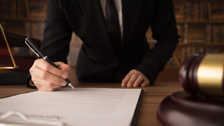 Herr im Anzug unterschreibt Vermögensauskunft in einem Gerichtssaal.