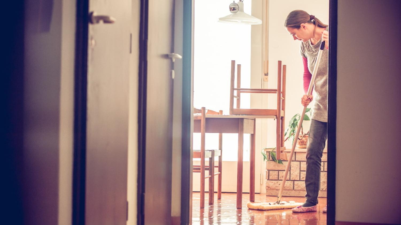 Eine Raumpflegerin wischt den Boden in einem Zimmer
