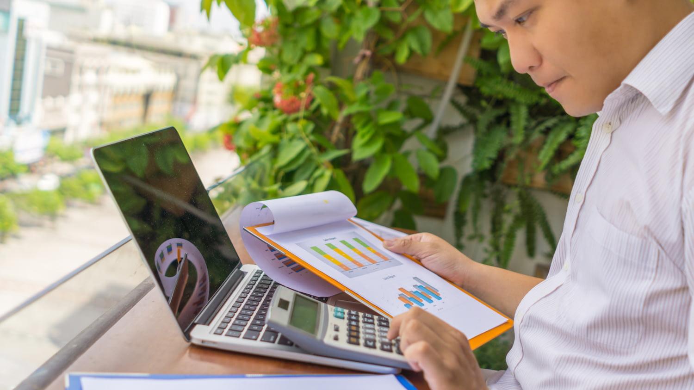 Junger Mann sitzt vor Taschenrechner und Laptop mit Papieren seiner Altersvorsorge