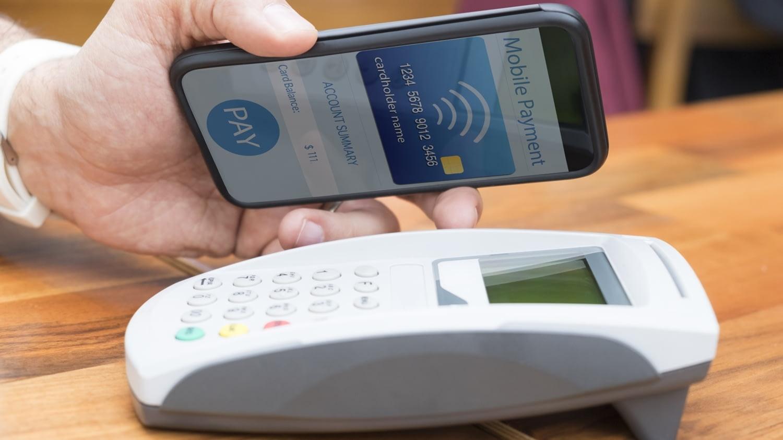 Mann hält Handy mit geöffneter Wallet-App über ein Lesegerät.